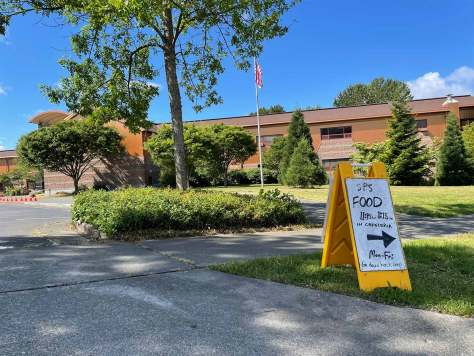 """Photo of exterior of Rising Star Elementary building with a yellow sign that reads """"SPS Food"""" and an arrow pointing towards the school."""