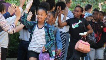 School-aged children of color smile and high-five a line of adults outside.
