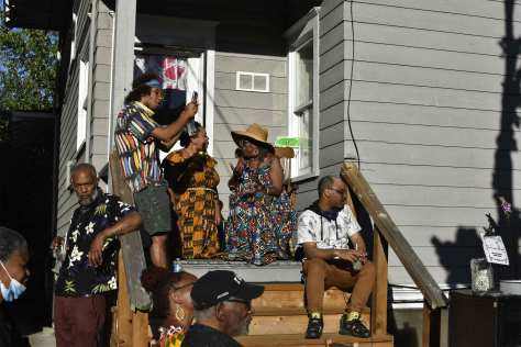 Individuals gathered on the porch of Wa Na Wari to celebrate Juneteenth outside with live music.