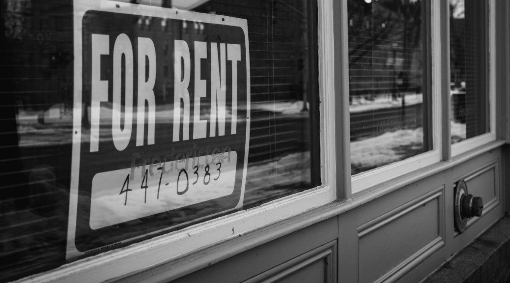 """Black-and-white photo of a """"For Rent"""" sign in a window."""