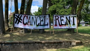 """Hand-painted banners that read """"#Cancel Rent"""" strung between posts in a park."""