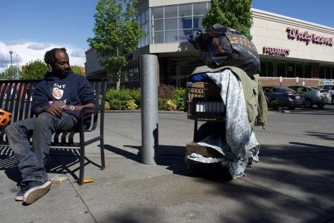 Photo of Holy next to his possessions in front of a Walgreens pharmacy.