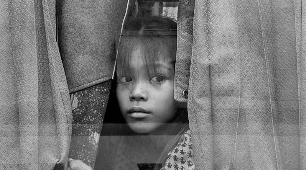 Black-and-white photo of a youth peering through a window behind hanging clothing.