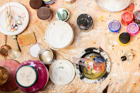 Photo of artist's supplies and spoons and paint on a stained light-colored tarp.