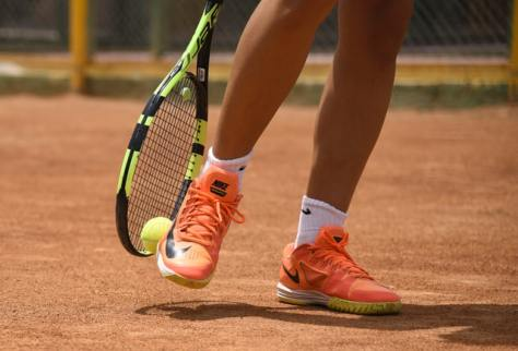 Photo of individual's orange tennis shoes holding a green tennis racket and tennis ball.