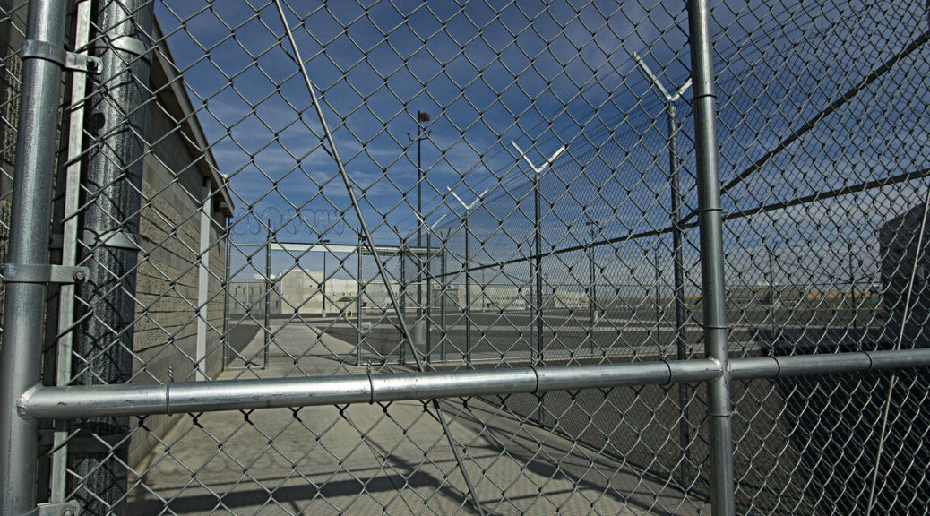 Photo depicting chain-link fencing surrounding a prison.