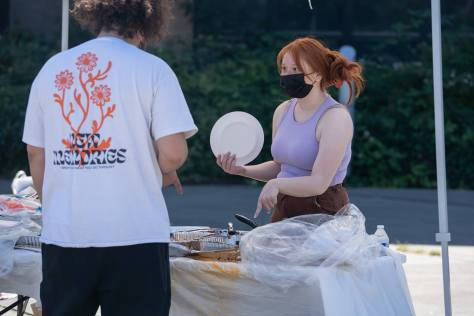 A youth volunteer helps hand out free food donated from local restaurants.