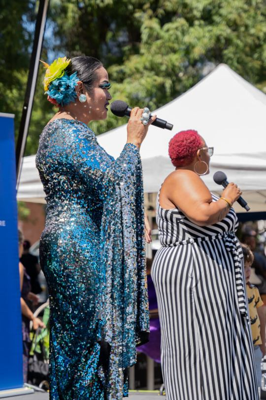 Photo of Aleksa Manila in a blue-sequined dress speaking into a microphone.