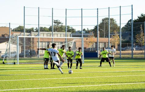 A Cham Bam! player shoots their penalty kick as Champa United FC players form a wall.