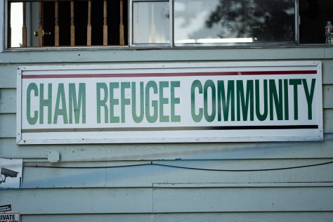 """A sign reading """"Cham Refugee Community"""" alongside the exterior of the CRC building."""