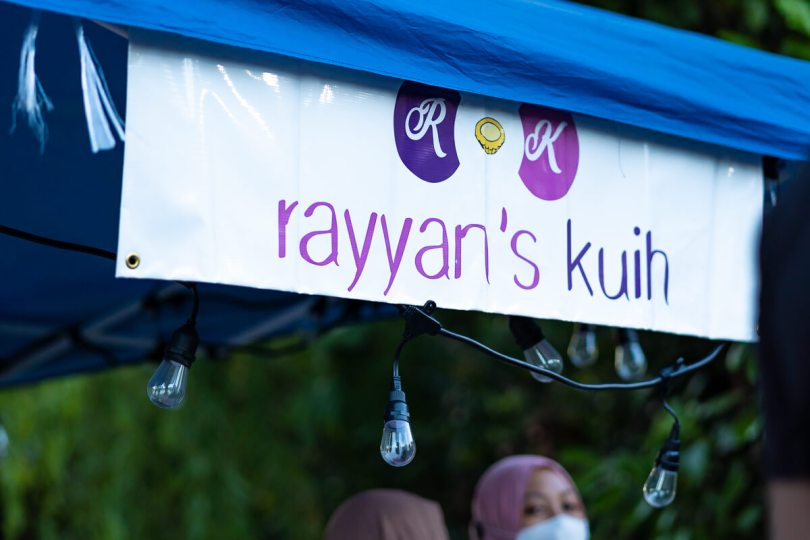 """A banner that reads """"Rayyan's Kuih"""" in purple lettering above the pop-up tent stall."""