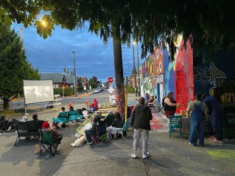 Photo depicting a movie screen with movie-goers sitting on outdoor chairs and picnic blankets at Feed the People Plaza.