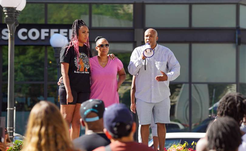 Ashley Paynter, @Decolonizingsci, comforts Kaloni Bolton's mother Kristina Williams while attorney James Bible, who represents Williams, talks about what happened to Kaloni and why the family wants accountability during the #BreatheforKaloni rally