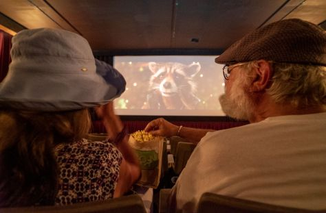 Photo from behind two individuals watching a preview on a movie theater screen and sharing popcorn.