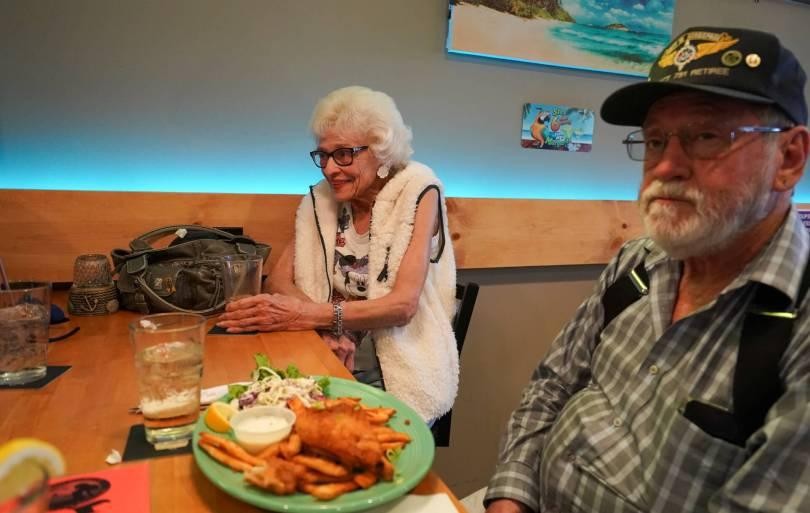 Two individuals sit at a bar table enjoying food.