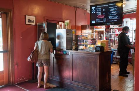 Photo of the interior of the Ark Lodge Theatre's concession stand. An individual grabs a drink from the soda machine while the concession stand seller prepares popcorn.