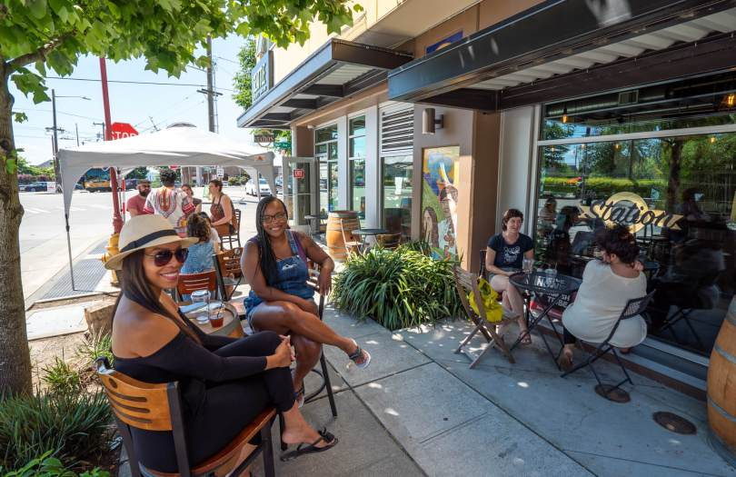 Zina Atwood and Leona Moore-Rodriguez, co-owner of The Station Coffee Shop, with her husband Luis, enjoy a beautiful July Saturday afternoon on the first weekend without COVID-19 restrictions.