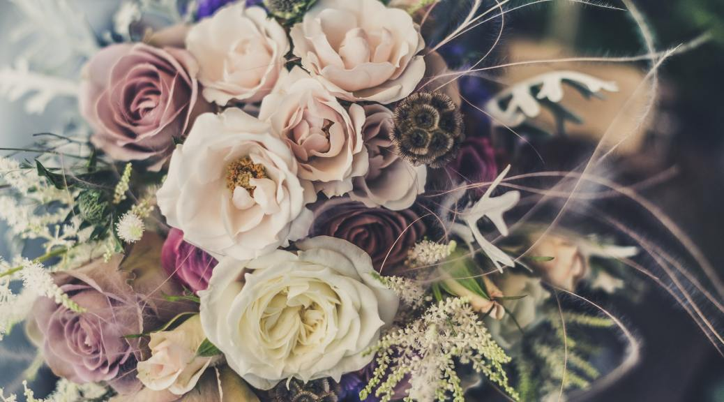A bouquet of pastel pink and purple roses and peonies.