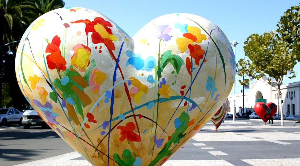 Photo of an outdoor artistic statue of a heart with splotches of brightly colored paint all over it.