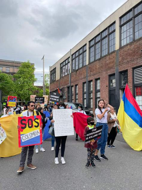 Photo depicting protestors preparing for a solidarity protest between Seattle and Colombia. Many protestors carry the Colombian flag or signs with the colors of the Colombian flag.