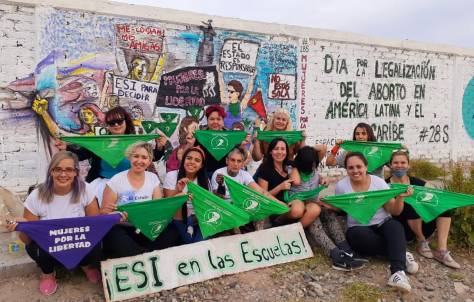 Women holding green triangle scarves, seated in front of a colorful mural calling for legalization of abortion.