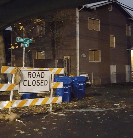 """Photo of a apartment building in Yesler Terrace on Alder Street. A """"Road Closed"""" sign blocks the street."""