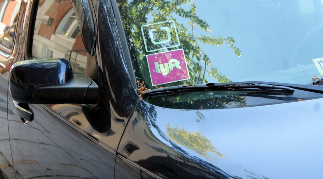 Photo of a car windshield with a Lyft logo and Uber logo sticker.