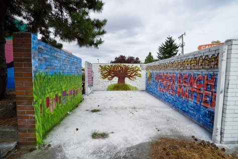 Photo depicting colorful and vibrant murals on brick walls adjacent to the Pho Van Restaurant building in Rainier Beach.