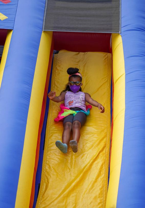 Photo of a female-presenting youth sliding happily down an inflatable slide.