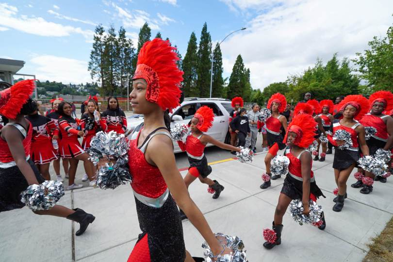 Photo of the Electronettes Drill Team in bright red and black sequined regalia with silver pom-poms walking down a sidewalk towards Jimi Hendrix Park.