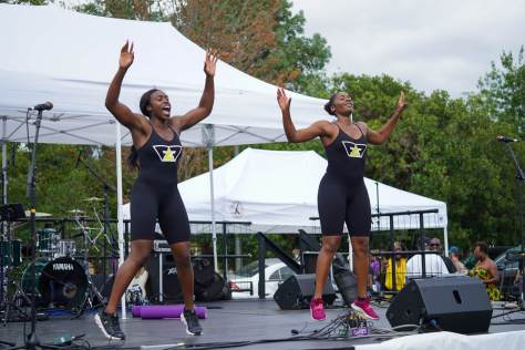 Photo of Free Flo Fit in black unitards doing jumping jacks on stage.
