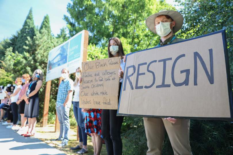 """Photo depicting staff members protesting outside Seattle Children's Hospital in Sandpoint with signs that read """"RESIGN"""" and """"Our Black patients, families, and colleagues deserve to feel safe at Seattle Children's. Our white male leaders have failed."""""""