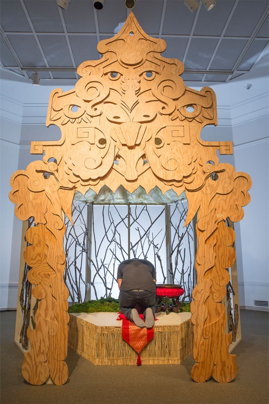 """Photo of Louis Chinn's artwork called """"The Oracle,"""" a carved wooden archway that opens to a raised enclosure with sculpted trees and grass. An individual is kneeling on the platform in prayer."""