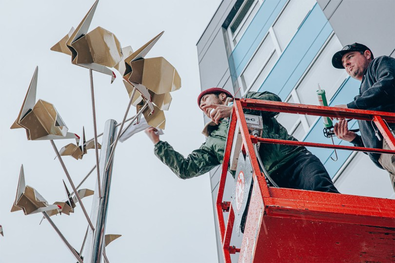 """Photo depicting Louis Chinn attaching origami-style cranes to the top of his """"Returning Home"""" sculpture."""