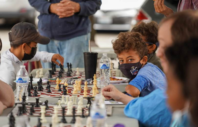 Photo of a long outdoor table with chess mats and individuals playing chess. A male-presenting youth looks towards the end of the table where the camera is.