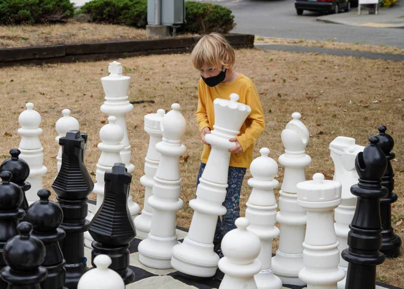 Photo depicting a sandy-haired youth in a yellow long-sleeved t-shirt attempting to move a white Queen chess piece nearly the same size as the youth on a giant chess board.