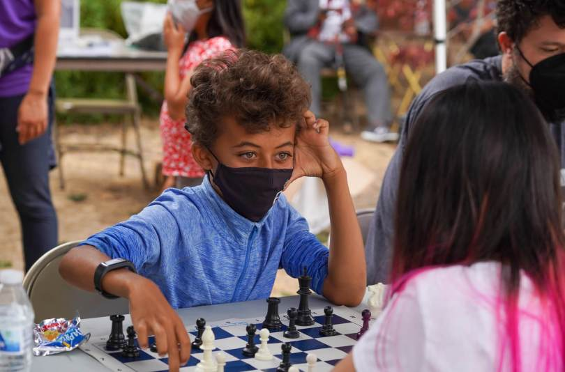 Photo of Yabi Ephrem talking to his opponent through a black surgical face mask during a game