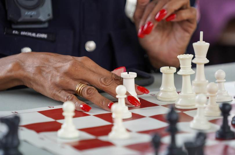 """Photo depicting Detective Denise """"Cookie"""" Bouldin's hands with bright red nail polish moving a white Rook chess piece on a board."""