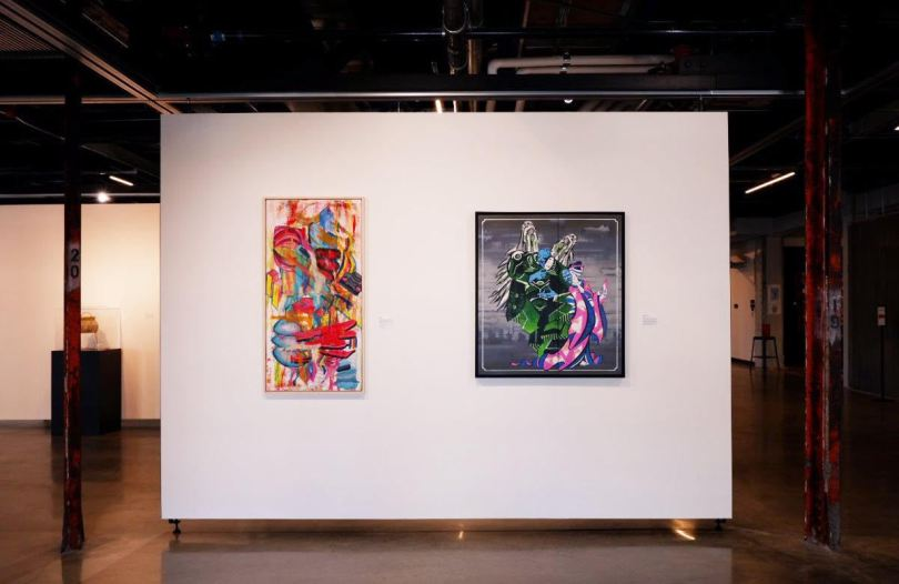 Photo of two art pieces side-by-side on a white wall in a gallery.