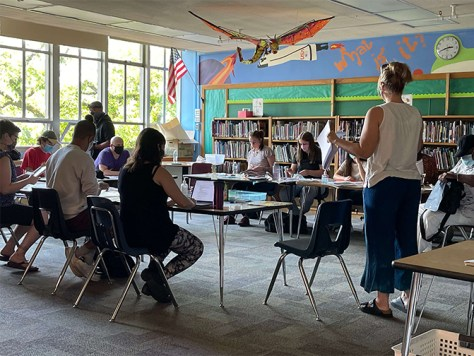 Photo of a classroom with teaching artists and assistants sitting at desks arranged in a circle reviewing orientation materials.