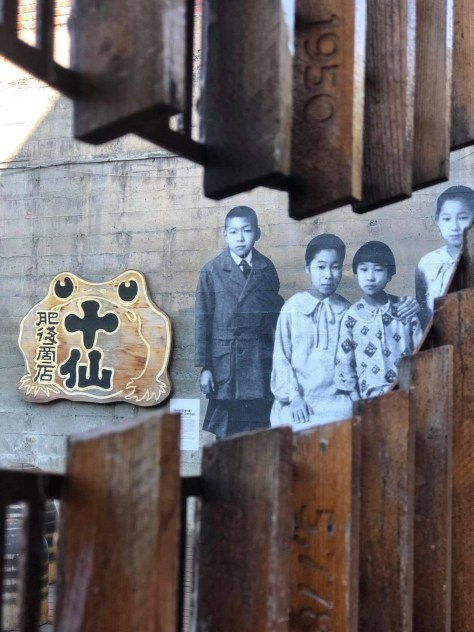Photo depicting an artistic wooden fence with a vintage photo of Japanese Americans on a wall between it. A golden frog with Japanese calligraphy characters on its belly sits on the wall beside the photo.