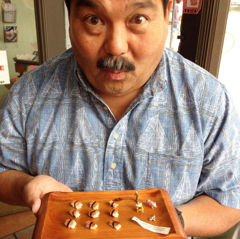 Photo depicting a male-presenting individual with a bushy mustache making a surprised face as he holds a platter of tiny spam nigiri sushi.