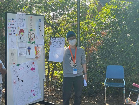 Photo of Dr. Saya Omori holding up a drawing next to a bulletin board full with colorful illustrations.