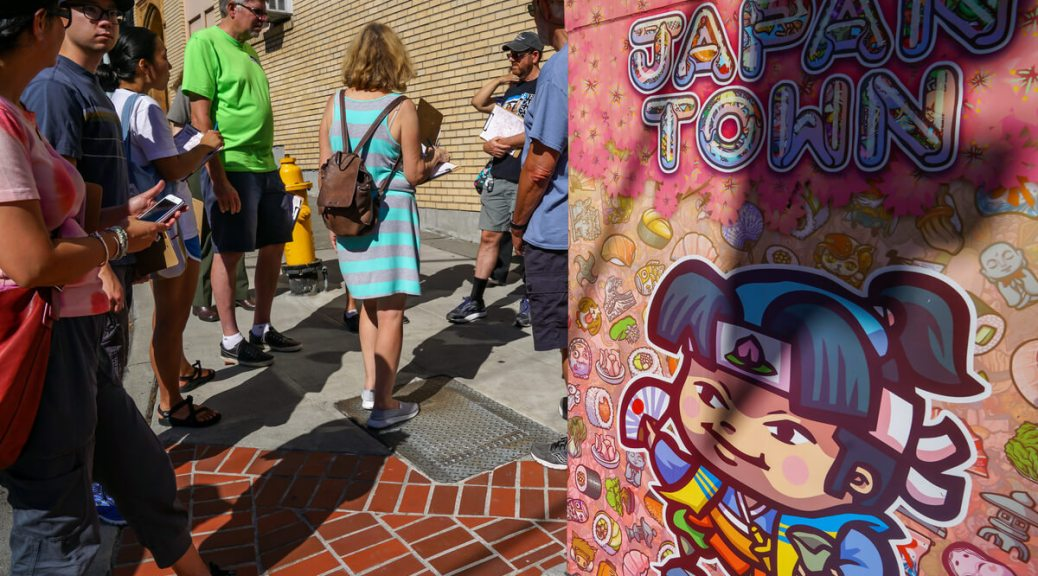 """Photo depicting a crowd gathering around a switching box with bright-pink and """"chibi"""" art on it."""