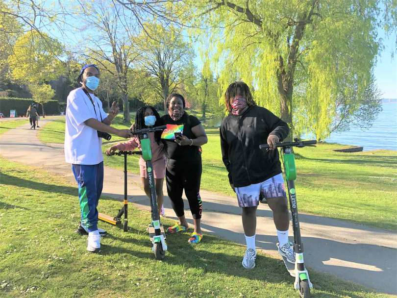 Photo of a Black-presenting family standing and smiling with Lime scooters along a tree-lined path and Lake Washington in the background.