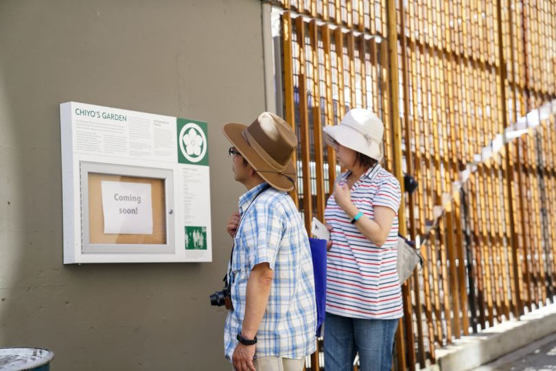 """Photo depicting two individuals in sun hats looking at an informational plaque titled """"Chiyo's Garden"""" in Nihonmachi Alley."""