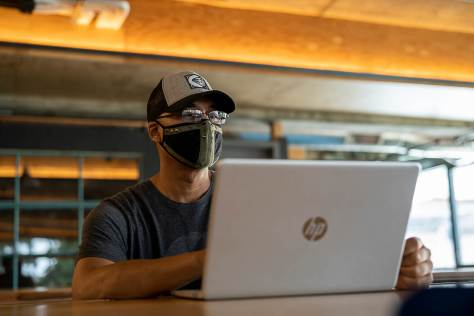 Photo depicting Ramon Shiloh sitting at a laptop computer with a cloth surgical mask covering his face.