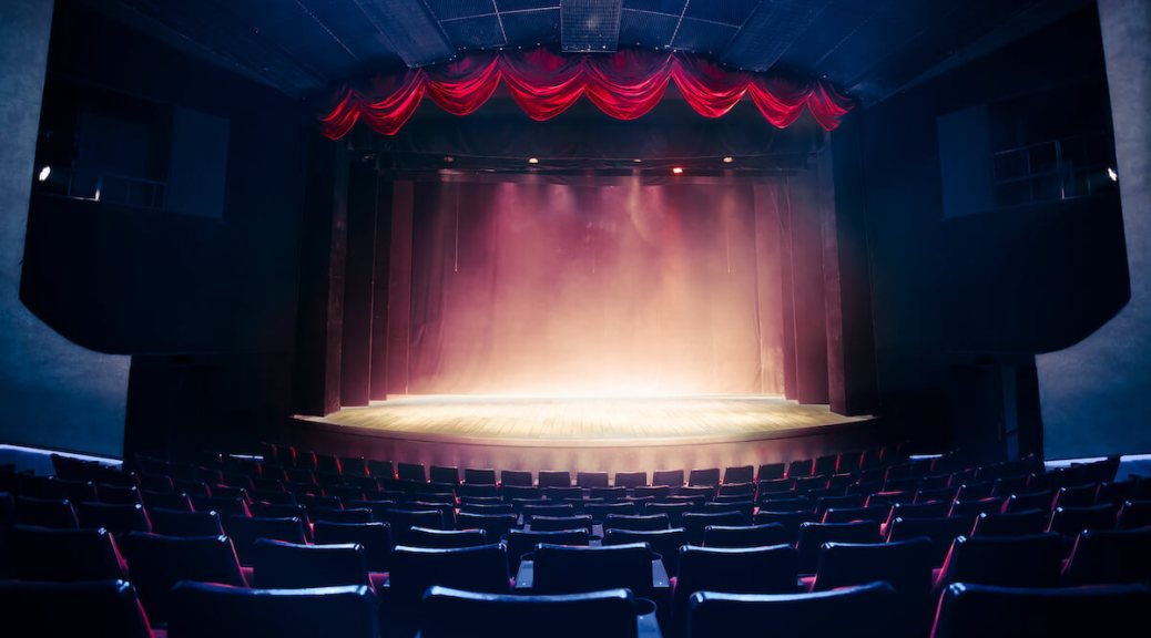 Photo depicting a theater curtain raised above a stage with dramatic lighting.