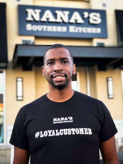 Photo of Todd Minor, waring a Nana's South Kitchen #LoyalCustomer t-shirt, stands out front of the restaurant.
