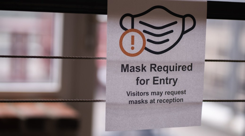 """Photo depicting an paper sign posted on an interior bannister that reads """"Mask required for Entry. Visitors may request masks at reception."""""""